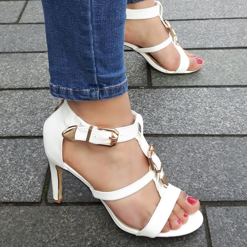 Witte sandalen met hoge hak en gouden gesp op de voet   Silhouette Hoge Hakken