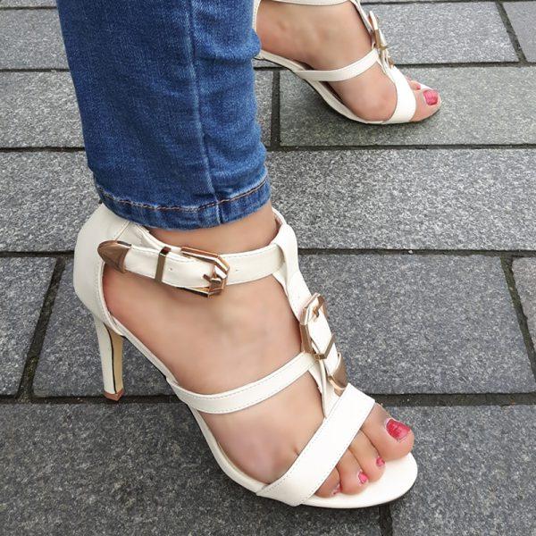 Sandalen in off white met hoge hak en gouden gesp op de voet